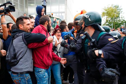 Civil Guard officers clash with members of the public at a polling station in Sant Julia de Ramis, Spain. Photo: Bloomberg