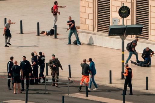French police examine the body of the attacker (right) who was shot dead by police after he stabbed a woman to death (left) outside the main train station in Marseille. Photo: Getty Images