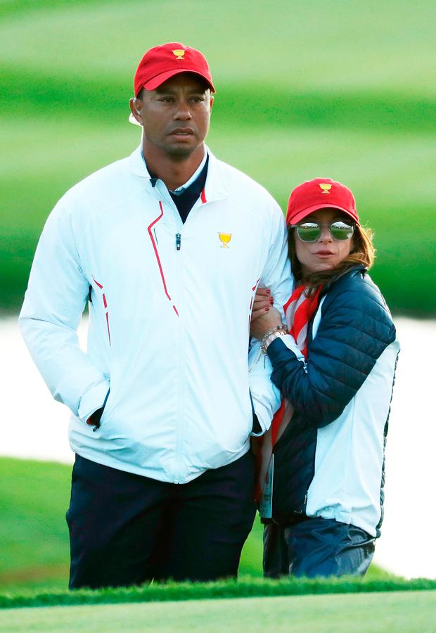 Tiger Woods of the U.S. Team and Erica Herman look on during Saturday four-ball matches of the Presidents Cup at Liberty National Golf Club on September 30, 2017 in Jersey City, New Jersey. (Photo by Rob Carr/Getty Images)