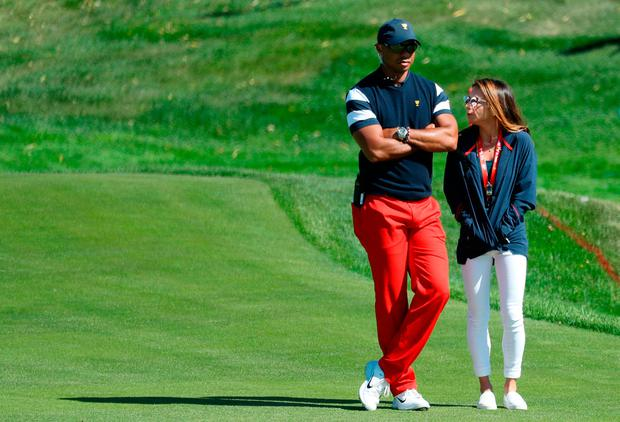 Captain's assistant Tiger Woods of the U.S. Team and Erica Herman walk on the first hole during Sunday singles matches of the Presidents Cup at Liberty National Golf Club on October 1, 2017 in Jersey City, New Jersey. (Photo by Rob Carr/Getty Images)