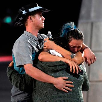 People hug and cry outside the Thomas & Mack Center after a mass shooting at the Route 91 Harvest country music festival on October 2, 2017 in Las Vegas, Nevada (Photo by Ethan Miller/Getty Images)