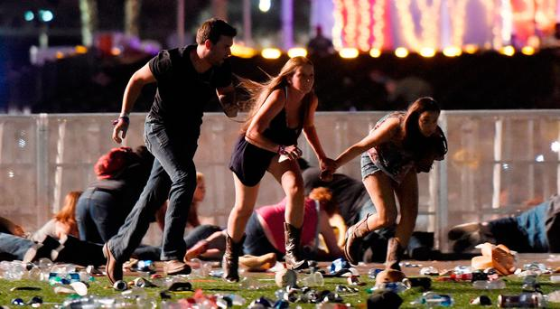People run from the Route 91 Harvest country music festival after apparent gun fire was hear on October 1, 2017 in Las Vegas, Nevada. (Photo by David Becker/Getty Images)