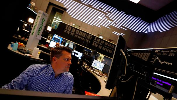 A share trader checks his screens at the stock exchange in Frankfurt