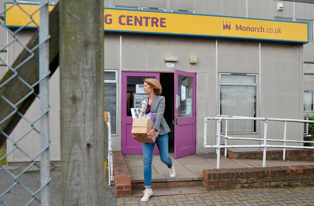 A woman carries a cardboard box out of a Monarch office after the airline ceased trading, at Luton airport