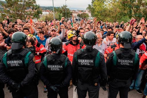 Police move back to their vans followed by members of the public after storming into polling station to confiscate ballot boxes and ballots in Sant Julia de Ramis, Spain. Photo: David Ramos/Getty Images