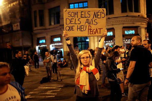 A demonstrator holds up a sign that reads,