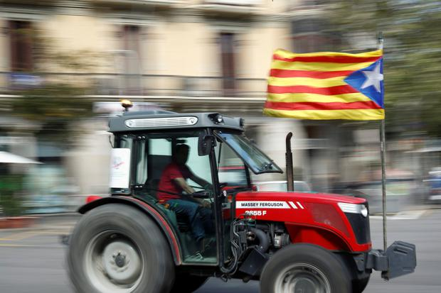 A farmer carries a Catalan separatist flag on his tractor during a protest to show support for the banned referendum on independence from Spain in Barcelona, Spain September 29, 2017. REUTERS/Juan Medina