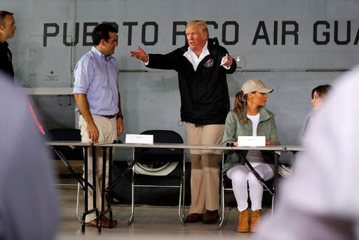 Puerto Rico Governor Ricardo Rossello (L) and U.S. President Donald Trump take their seats for a briefing on hurricane relief efforts in a hangar at Muniz Air National Guard Base in Carolina, Puerto Rico, U.S. October 3, 2017. REUTERS/Jonathan Ernst