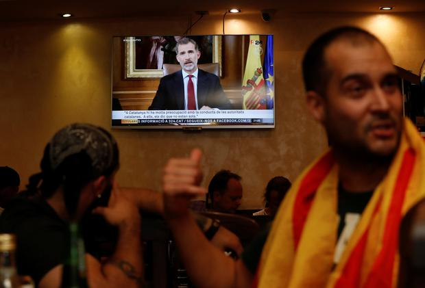Patrons in a restaurant watch as Spanish King Felipe makes a televised address to the nation in Barcelona, Spain, October 3, 2017. REUTERS/Yves Herman