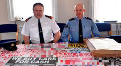 Superintendent Thomas Murphy and Sgt Peter Woods with some of the signs seized as part of Operation Sign-Off