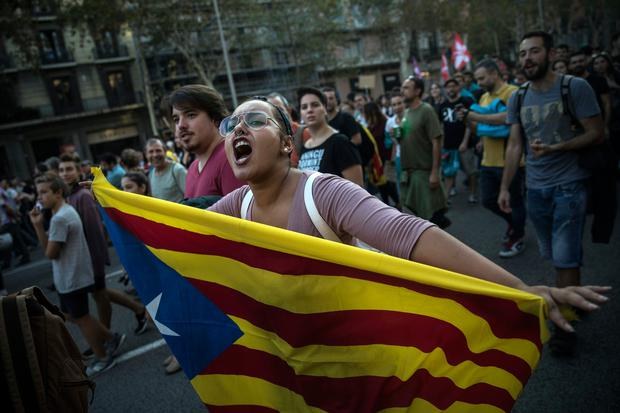 A woman carries an independence Catalan flag as demonstrators march downtown Barcelona, Spain, Tuesday Oct. 3, 2017 (AP Photo/Santi Palacios)