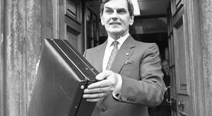 Ray MacSharry, Minister for Finance, holds aloft the Budget Bag.