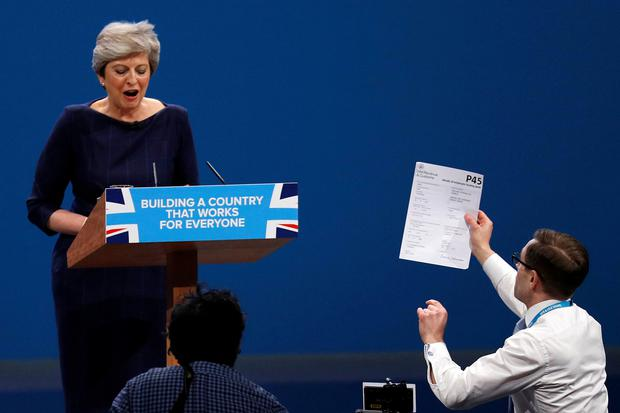 A member of the audience hands a P45 form (termination of employment tax form) to Britain's Prime Minister Theresa May as she addresses the Conservative Party conference in Manchester, October 4, 2017. REUTERS/Phil Noble