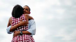 First Lady Michelle Obama (L) and US President Barack Obama (R) hug after delivering remarks during a campaign event at the Alliant Energy Amphitheater in Dubuque, Iowa, August 15, 2012, during his three-day campaign bus tour across the state. AFP PHOTO/Jim WATSON / AFP / JIM WATSON