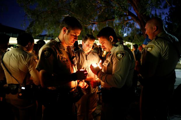 Police officers hold candles during a vigil for the victims of a mass shooting at the Route 91 Harvest Country Music Festival in Las Vegas, Nevada, U.S., October 3, 2017. REUTERS/Chris Wattie