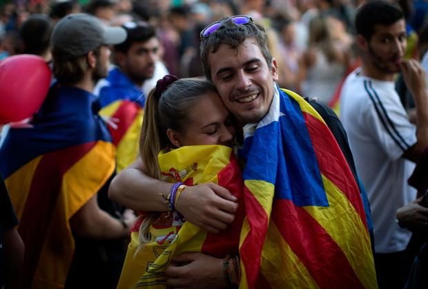 Childhood friends David Jovellar (24), wearing an independence flag, and Almudena Chueco (23), wearing a Spanish flag, hug at a rally in Barcelona, Spain. Photo: PA