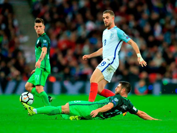 Slovenia's Bojan Jokic (left) and England's Jordan Henderson (right) battle for the ball. Photo: Adam Davy/PA Wire