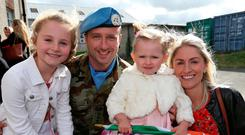 Capt Gary Ryan from Kildare is greeted by his wife Edel and daughters, Molly (7) and Ella (2) at Casement Aerodrome as he returned home following a six-month deployment Photo: Collins