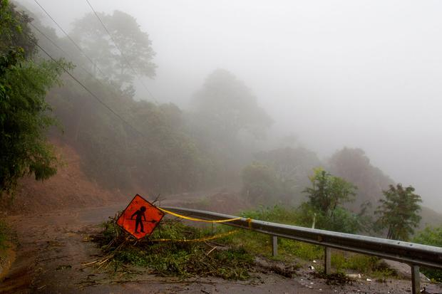 A men at work sign stands on a washed out road in Alajuelita on the outskirts of San Jose, Costa Rica, Thursday, Oct. 5, 2017 (AP Photo/Moises Castillo)