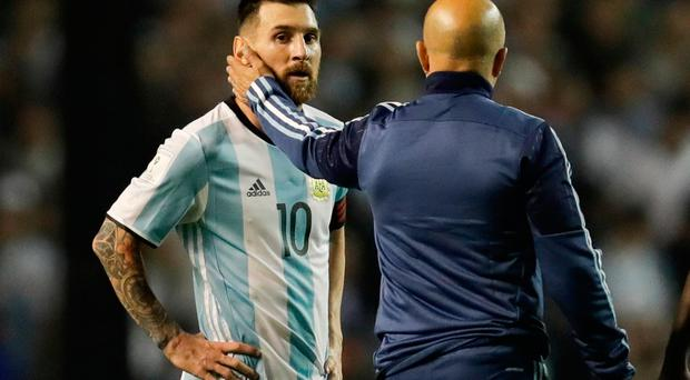 Argentina's Lionel Messi, left, is comforted by Argentina coach Jorge Sampaoli