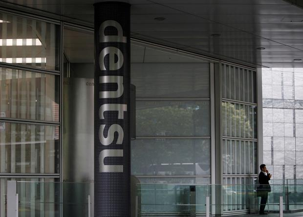 A man speaks on his mobile phone near a logo of Dentsu Co. at the entrance of the company headquarters in Tokyo July 12, 2012. REUTERS/Issei Kato/File Photo