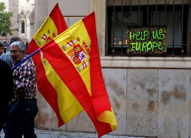Pro-union supporters walk past a home made appeal for help during a demonstration in a square in Sabadell, Calatonia, Spain, October 6, 2017. REUTERS/Juan Medina