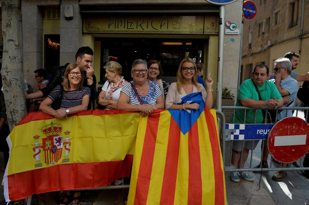 People stand behind Spanish (L) and Estelada (Catalan separatist flag) flags as Spanish National Police officers leave their hotel in Reus, south of Barcelona, Spain October 5, 2017. REUTERS/Vincent West