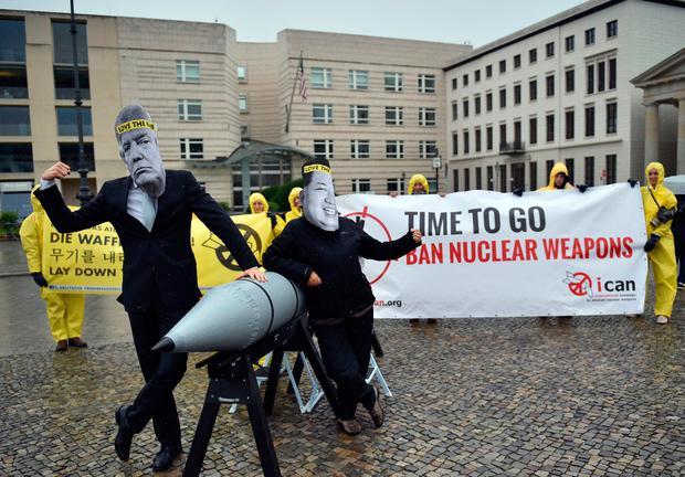 Activists of the International Campaign to Abolish Nuclear Weapons (ICAN) protest against the conflict between North Korea and the USA with masks of the North Korean ruler Kim Jong Un, right, and the US president Donald Trump, left, in front of the US embassy in Berlin, Germany. Photo: Britta Pedersen/dpa via AP