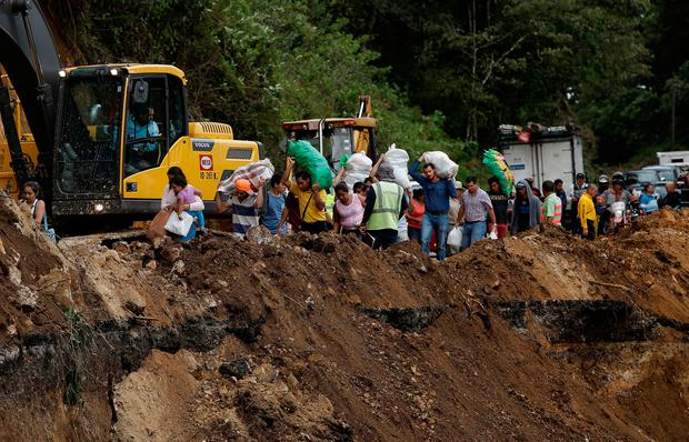 People traveling by bus for two days and were trapped between landslides walks in an area of a highway collapsed by Storm Nate in Casa Mata, Costa Rica October 6, 2017. REUTERS/Juan Carlos Ulate