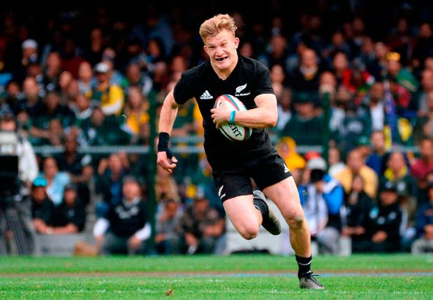 New Zealand's Damian Mckenzie runs with the ball on his way to score a try during the Rugby test match between South Africa (Springboks) and New Zealand (All Blacks) at Newlands Rugby stadium on October 7, 2017 in Cape Town. / AFP PHOTO / RODGER BOSCHRODGER BOSCH/AFP/Getty Images