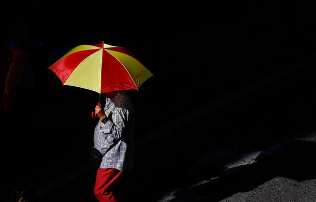 A man carries an umbrella in the colors of the Spansh flag as demonstrators gathered for a pro-union demonstration organised by the Catalan Civil Society organisation in Barcelona, Spain, October 8, 2017. REUTERS/Juan Medina