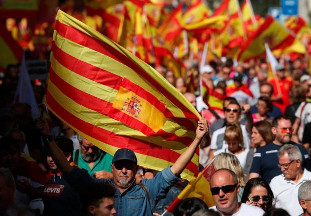 People wave Spanish and Catalan flags as they attend a pro-union demonstration organised by the Catalan Civil Society organisation in Barcelona, Spain, October 8, 2017. REUTERS/Albert Gea