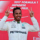 Mercedes driver Lewis Hamilton of Britain poses on the podium after winning the Japanese Formula One Grand Prix. Photo: Toru Takahashi