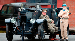 Military re-enactors, husband and wife Kevin and Maura McCormack, rest on the historic Sliabh na mBan armoured Rolls Royce used by Michael Collins