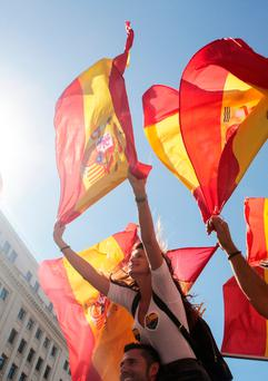 A woman holds a Spanish flag during a pro-union demonstration organised by the Catalan Civil Society organisation in Barcelona. Picture: Reuters