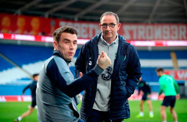 Seamus Coleman delivers the good news that Scotland had only drawn with Slovenia to Ireland manager Martin O'Neill during a training session at the Cardiff City Stadium. Photo: PA