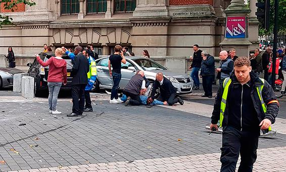 A man is restrained alongside crashed vehicles after the incident in South Kensington, London, on Saturday afternoon. Photo: Getty Images