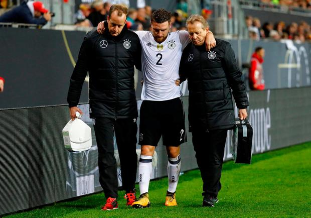 Germany's Shkodran Mustafi receives medical attention after sustaining an injury last night. REUTERS/Kai Pfaffenbach