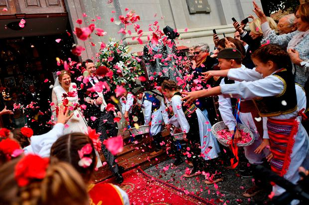 Guests throw rose petals at Prince Philip of Serbia, also known as Filip Karadjordjevic and his bride Danica Marinkovic as they exit the Belgrade cathedral following their wedding ceremony on October 7, 2017.