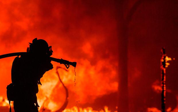 A firefighter pulls a hose in front of a burning house in the Napa wine region of California on October 9, 2017, as multiple wind-driven fires continue to whip through the region. / AFP PHOTO / JOSH EDELSONJOSH EDELSON/AFP/Getty Images