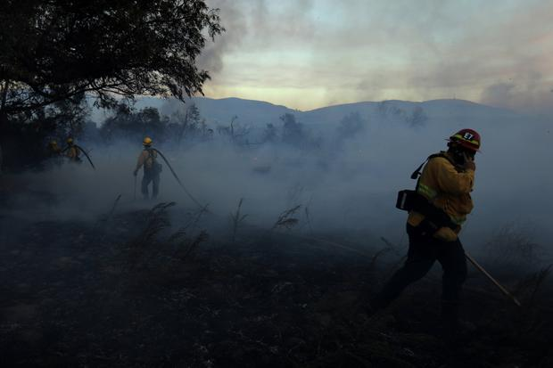 Firefighters work to put out hot spots on a fast moving wind driven wildfire in Orange, California, U.S., October 9, 2017. REUTERS/Mike Blake