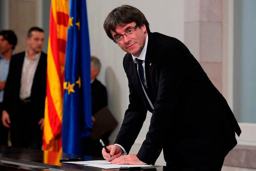 Catalan president Carles Puigdemont signs a declaration of independence at the regional parliament in Barcelona. Photo: Getty