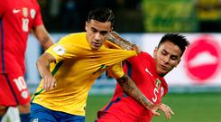 Brazil's Philippe Coutinho (L) is tackled by Erick Pulgar of Chile during Tuesday night's World Cup qualifier Photo: Getty