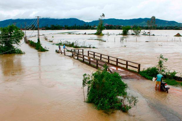 This picture from the Vietnam News Agency taken on October 11, 2017 shows a man (R) walking with his motorcycle through a flooded area in the central province of Nghe An. AFP PHOTO / Vietnam News Agency / VIETNAM NEWS AGENCYVIETNAM NEWS AGENCY/AFP/Getty Images
