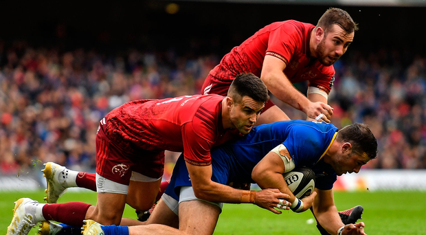 Robbie Henshaw of Leinster is tackled by Conor Murray and JJ Hanrahan of Munster