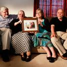 In this June 4, 2014, file photo, from left, Patrick Boyle, Linda Boyle, Lyn Coleman and Jim Coleman hold photo of their kidnapped children, Joshua Boyle and Caitlan Coleman, who were kidnapped by the Taliban in late 2012, Wednesday, June 4, 2014, in Stewartstown, Pa. (AP Photo/Bill Gorman, File)