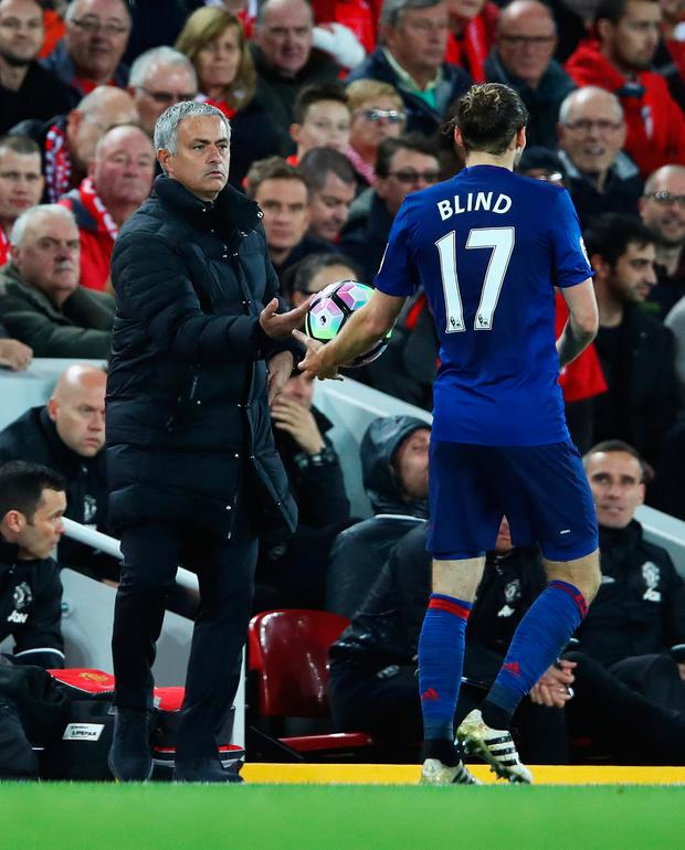 Jose Mourinho hands the ball to Daley Blind during Manchester United visit to Anfield last season, which finished scoreless. Photo: Getty