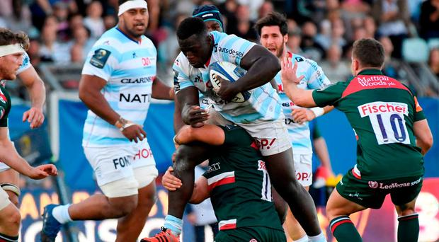 Racing 92's Portuguese prop Cedate Gomes Sa (C) is tackled by Leicester's British prop Greg Bateman