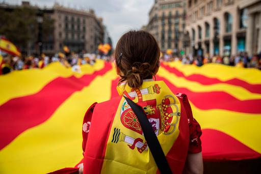 True colours: A woman wearing a Spanish flag on her shoulders looks at a giant flag of Catalonia as people celebrate a holiday known as Dia de la Hispanidad, or Spain's National Day, in Barcelona last Thursday, amid one of the country's biggest crises ever as the north-eastern region threatens independence. Photo: AP