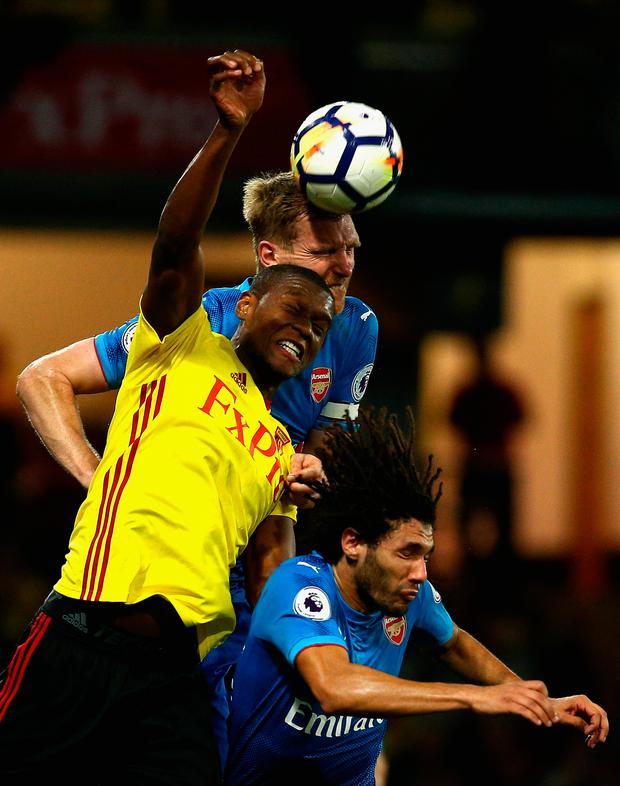 Christian Kabasele of Watford jumps between Per Mertesacker and Mohamed Elneny of Arsenal. Photo: Getty Images